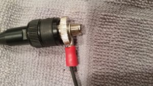 The antenna connector is shown in a close up with the rat tail O connector with wire slid into the ground of the antenna.