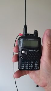 The image shows a person holding a HT radio and comming off the antenna connection base is the rat tail wire ground.